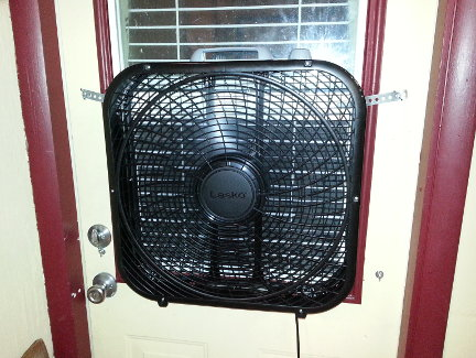 A fan installed in the window of the side door to the garage.